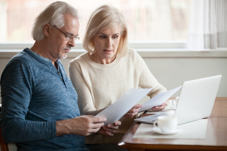 Senior couple reading documents about revocable and irrevocable trusts