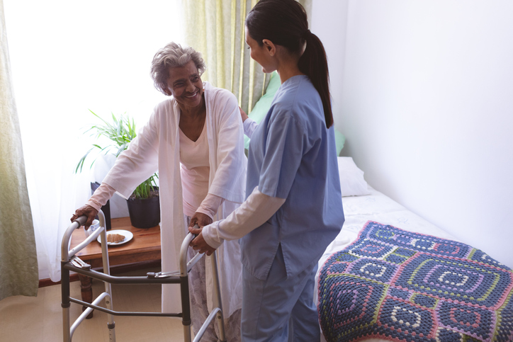 Female nurse helping senior female nursing home patient to stand with walker