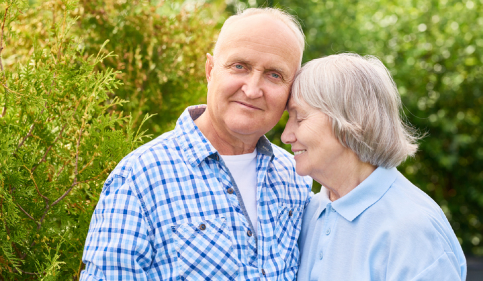Long-term care planning concept: Portrait of loving senior couple embracing tenderly posing for camera in beautiful garden
