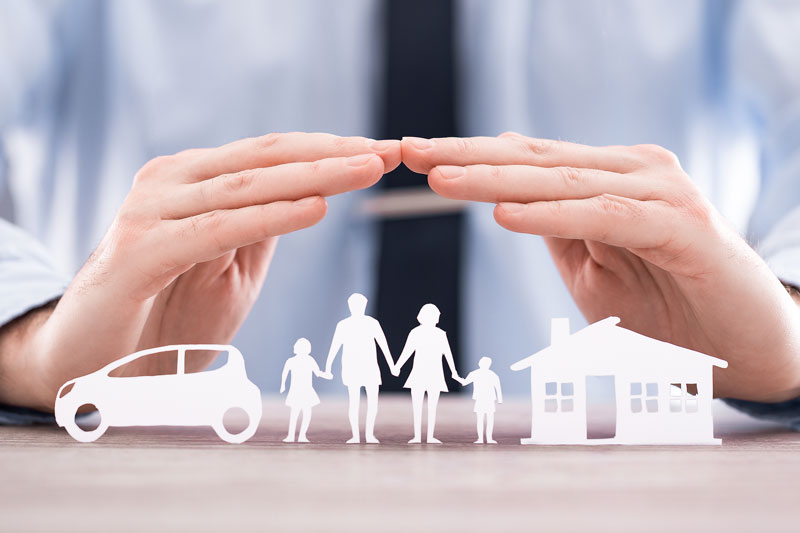 Asset protection. Businessman holding hands over paper cutouts of a family, car and home