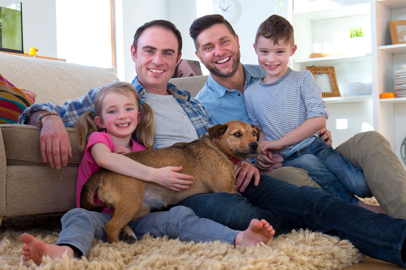 Estate Planning. Male couple posing with son, daughter and dog