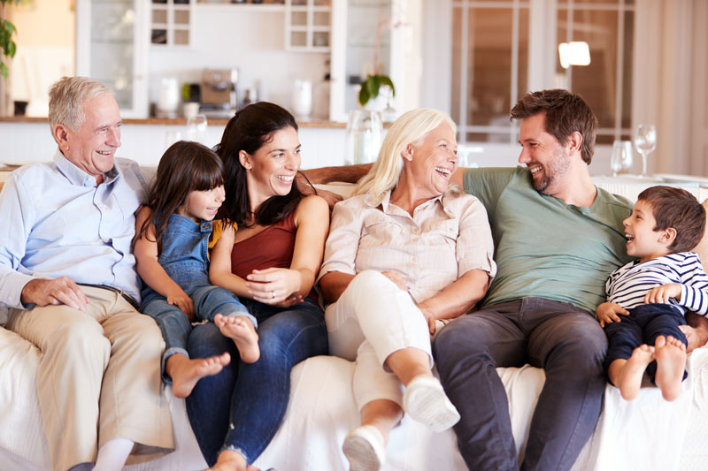 multi-generational family sitting on couch laughing