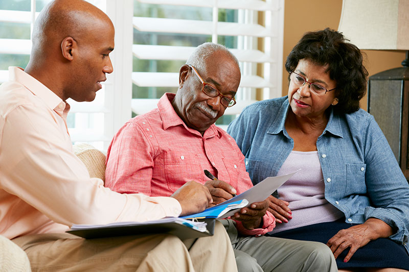 Medicaid planning. Senior couple looking over paperwork with their estate planning attorney