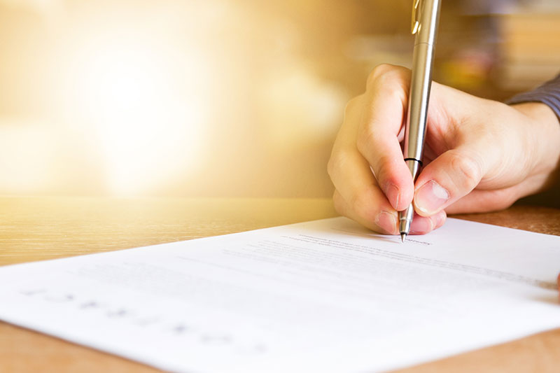 business man signing probate and trust administration document on office desk