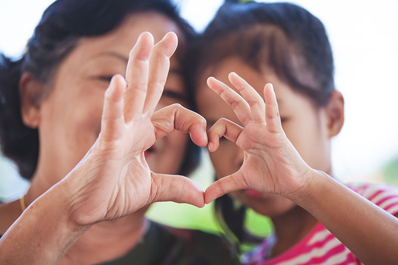 Asian grandmother and little girl with special needs making heart shape with hands together with love